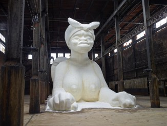 Kara Walker: A Subtlety, or the Marvelous Sugar Baby, an Homage to the unpaid and overworked Artisans who have refined our Sweet tastes from the cane fields to the Kitchens of the New World on the Occasion of the demolition of the Domino Sugar Refining Plant, 2014. Polystyrene foam, sugar Approx. 35.5 x 26 x 75.5 feet (10.8 x 7.9 x 23 m). A project of Creative Time, installation view: Domino Sugar Refinery, Brooklyn, NY, 2014. Photo: Jason Wyche. Artwork © 2014 Kara Walker.
