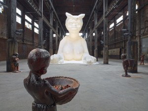 Kara Walker: At the behest of Creative Time Kara E. Walker has confected: A Subtlety, or the Marvelous Sugar Baby, an Homage to the unpaid and overworked Artisans who have refined our Sweet tastes from the cane fields to the Kitchens of the New World on the Occasion of the demolition of the Domino Sugar Refining Plant. A project of Creative Time, installation view: Domino Sugar Refinery, Brooklyn, NY, 2014. Photo: Jason Wyche. Artwork © 2014 Kara Walker.